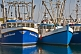 Image of Three blue fishing boats moored to the wharf.
