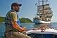 Image of Man in small motor boat watches the square rigger \\\\'Picton Castle\\\\' as she sets sail towards the ocean.