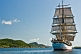 Image of The tallship 'Picton Castle' leaves harbor on a sunny morning under full sail.