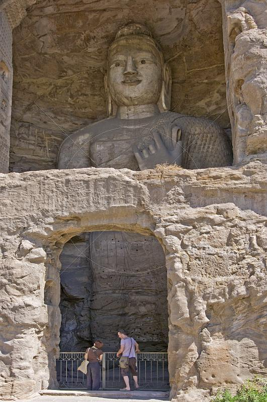 Two western tourists looking at a giant Buddha statue at the Yungang Buddhist caves, near Datong.