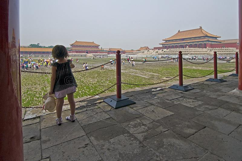 A small Chinese girl watches tourists in the Forbidden City.