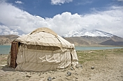 A yurt next to Karakul Lake on the Karakoram Highway, with view of the snow-capped Pamir mountains.