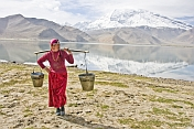 Woman carrying water from Karakul Lake, near the Karakoram Highway, with view of the snow-capped Pamir mountains.