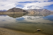 A snow-capped Pamir mountain reflection in Karakul Lake, near the Karakoram Highway between Kashgar and Tashkurgan.