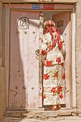 Uighur woman in white and red skirt and top, standing in pink doorway.