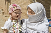 Uighur woman wearing headscarf, with small child.