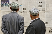 Two Uighur men read the local-language newspapers.