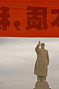 Statue of Chairman Mao Tsedong under red banner with Chinese characters.