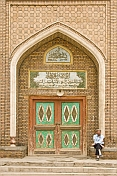 Muslim man sitting next to the entrance door to a mosque.