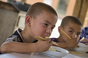 Boys eating noodles at the Gaochang (Khocho) ruins near Turpan.
