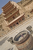Incense burns in front of the multi-layered roofs that protect access to the Buddhist Mogao Caves.