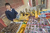 Chinese lady with calculator selling Chinese curios and souvenirs.