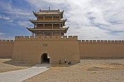 Two workers repair the paths in front of the main gateway to the Jiayuguan Fort.