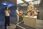 Chinese and Western visitors admire a kneeling Terracotta Archer.