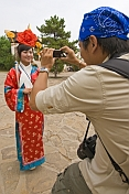 Chinese tourist photographing Putuozongcheng Buddhist Temple girl.
