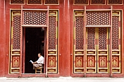 Man reading paper at the Buddhist Temple of Sumeru Happiness and Longevity.