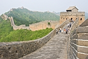 Western and Chinese visitors walk along the Great Wall of China.