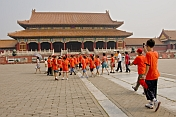 Chinese school-children in orange teeshirts visit Gate of Supreme Harmony at the Forbidden City.