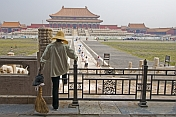 A cleaner watches tourists at the Hall of Supreme Harmony in the Forbidden City.