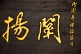 Image of Gold Chinese characters on a black wooden background.