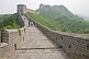 Image of Western and Chinese visitors walk along the Great Wall of China.