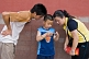 Image of Two Chinese tourists examine their son\\\\'s digital camera in the Forbidden City.
