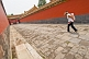 Image of Chinese tourist woman carrying child down a passage to the Imperial Living Quarters in the Forbidden City.