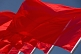 Image of Red Chinese flags billowing in the wind of Tiananmen Square.