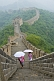 Image of Two Chinese ladies with umbrellas walk along the Great Wall of China.