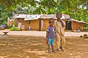 Two small brothers stand in front of their mud brick house.