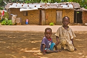 Two small brothers kneel in front of their mud brick house.