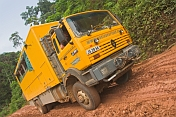 Oasis Overland truck drives through muddy section of jungle logging road.