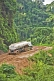 A white fuel tanker struggles to drive along muddy logging roads in the dense jungle.