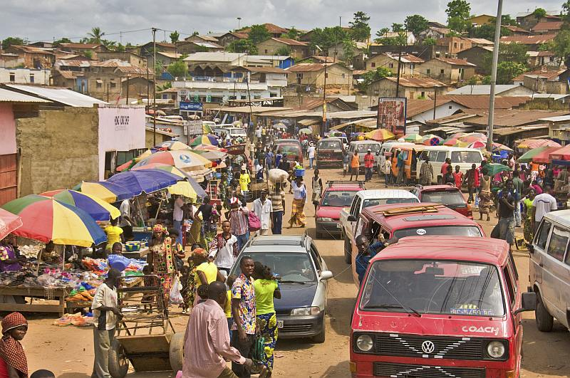 Heavy traffic and colorful market stalls pack the main street.