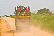 A heavily laden truck with passengers riding on top of the cargo drives down a dusty main road.