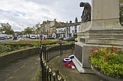 War Memorial with commemorative wreaths on roundabout in the High Street.