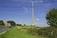 Image of The 330m 1080 feet high Emley Moor TV transmission tower dominates nearby road and houses.