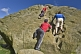 Image of Climbers in red and blue shirts climb the Cow and Calf Rocks on Ilkley Moor.