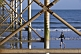 Image of Girl walks on beach under Teignmouth Pier.